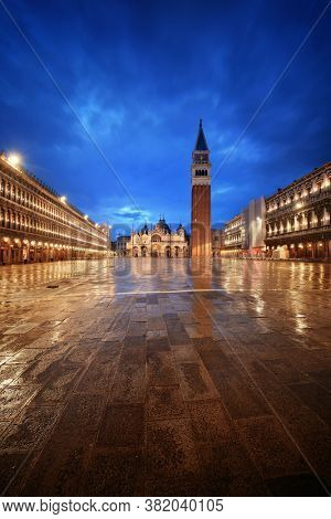 Bell tower and historical buildings at night at Piazza San Marco in Venice, Italy.