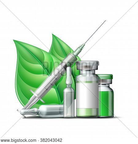 Medical Syringe With Green Liquid And Medicine Ampoules And Vials With Green Leaves.