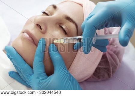 Subcutaneous Injection Into Girl's Face. Doctor Cosmetologist Doing Pull-injection In Face Model.