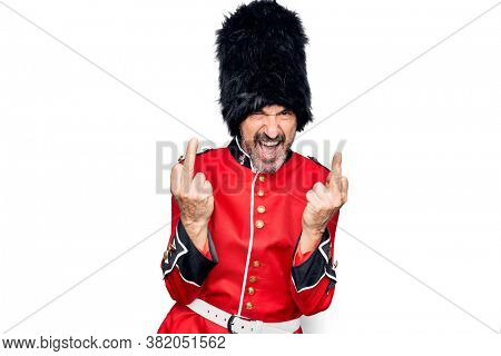 Middle age handsome wales guard man wearing traditional uniform over white background Showing middle finger doing fuck you bad expression, provocation and rude attitude. Screaming excited