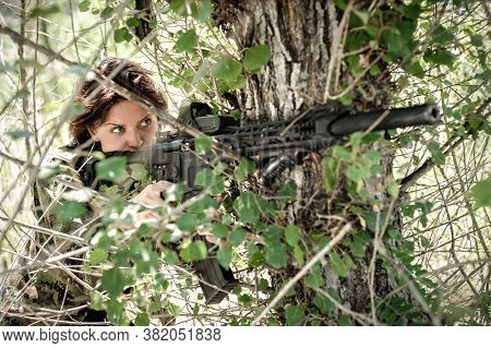 Attractive Woman Soldier Shooting With Rifle Machine Gun In Forest