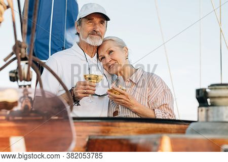 Mature Couple Standing On A Private Yacht And Drinking Wine. Two Senior People Enjoy Sailing And Eac