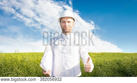 Builder Wearing In White Helmet With Project On Hand In Good Mood In Green Field. Worker With Projec