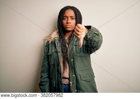 Young african american woman wearing winter parka coat over isolated background looking unhappy and angry showing rejection and negative with thumbs down gesture. Bad expression.