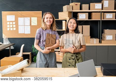 Two young cheerful female workers of online shop office standing by table against large wooden shelves with packed boxes and noticeboard