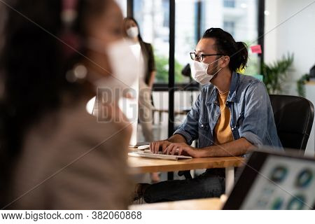Asian Office employee with protective face mask working in new normal office with social distance practice to african colleague in foreground prevent coronavirus COVID-19 spreading.