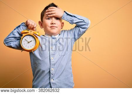 Young little boy kid holding classic bell alarm clock over isolated yellow background stressed with hand on head, shocked with shame and surprise face, angry and frustrated. Fear and upset for mistake
