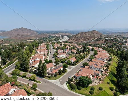 Aerial View Of Middle Class Neighborhood With Residential House Community And Mountain On The Backgr