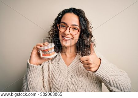 Young beautiful woman with curly hair holding plastic teeth with dental baces happy with big smile doing ok sign, thumb up with fingers, excellent sign