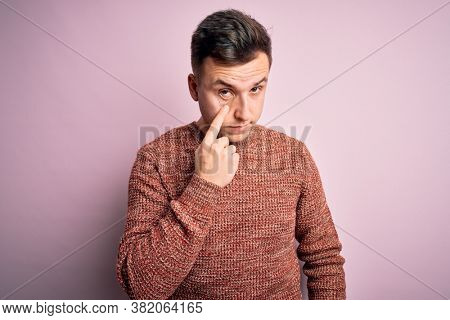 Young handsome caucasian man wearing casual winter sweater over pink isolated background Pointing to the eye watching you gesture, suspicious expression
