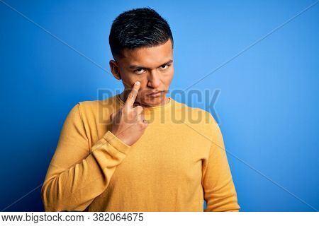 Young handsome latin man wearing yellow casual sweater over isolated blue background Pointing to the eye watching you gesture, suspicious expression