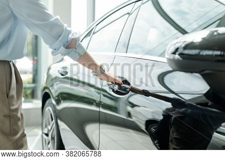Hand of young elegant man in shirt and trousers standing by luxurious black car and holding by handle while going to open one of doors