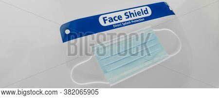 PPE for covid and corona virus. Medical mask and face shield protective equipment for healthcare workers and business. Panoramic banner crop of face covering protection.