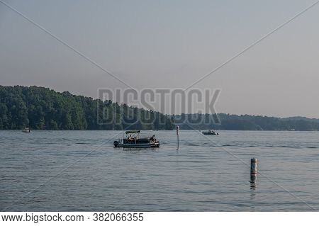 On A Hot Hazy Day On The Lake With Lots Of Boating Activities With People Fishing And Speeding By On