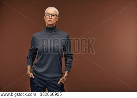 Young stylish female in dark grey pullover, black trousers and eyeglasses keeping her hands in pockets while standing in front of camera