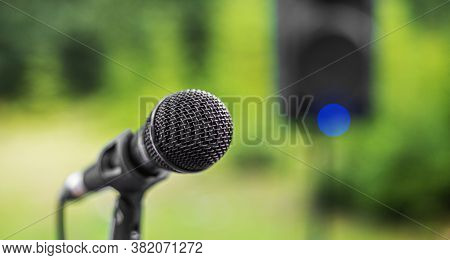 Black Microphone On A Stand Against The Background Of A Loudspeaker.