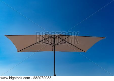 Bottom View. Beach Umbrella Against A Blue Cloudless Sky. Sun Protection On The Beach.