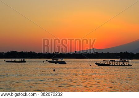 Scenic beach with boats silhouetted at sunset on a tropical island of Indonesia