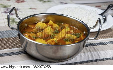 Pot Of Potato Chunks Cooked In Tomato Gravy And Granished With Coriander Leaves. Served Along With S