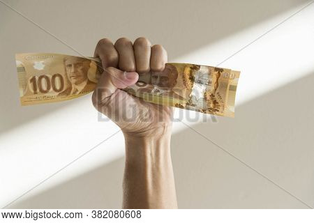 Hand Tight Fist Squeezing Canadian Dollar Bills.