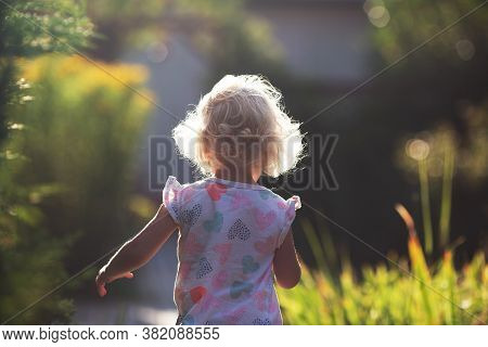 Backview Of Happy Cheerful Small Girl With Blond Curly Hair Running In The Garden In Sunny Summer Da
