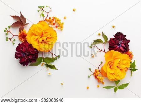 Autumn composition with flowers, leaves and berries on white background. Flat lay, copy space.