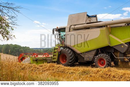 Combine Harvester Harvests Ripe Wheat In Field Of Trees And Beautiful Blue Sky With Clouds. Reaping