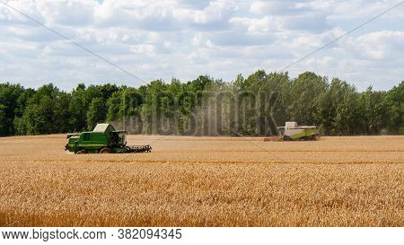 Two Modern Combines At Work In Field During Wheat Harvesting Season Go Towards Each Other. Harvester
