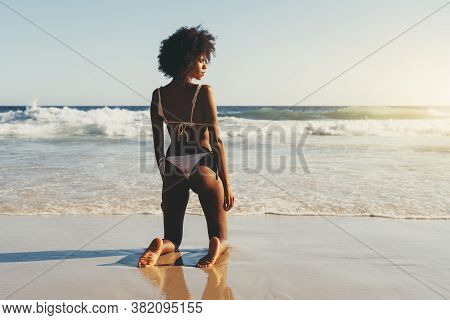 View From Behind Of A Cute Young African-american Woman With A Curly Afro Hair Standing On Her Knees