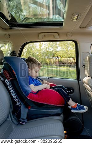 Preschool Cute 3-4 Years Old Boy Sitting In Safety Car Seat And Crying During Family Travel By Car,
