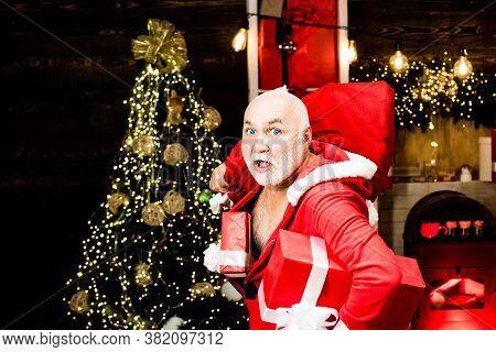 Burglar Man Dressed In Santa Wearing A Santa Hat. Thief Santa With Bag On Christmas Background. Thie