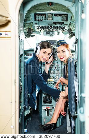 Two Young Girls In Aircraft. Young Woman Pilot With Headset. Beautiful Smiling Women Pilot With Head