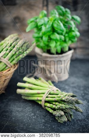 Fresh raw organic green Asparagus sprouts closeup. Over wooden table. Healthy vegetarian food. Raw vegetables, market. Healthy eating, diet, dieting concept
