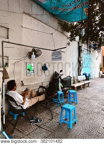 Saigon, Vietnam - January 27, 2020: Local Barber Chilling At Hi Barber Shop On The Streets Of Ho Chi