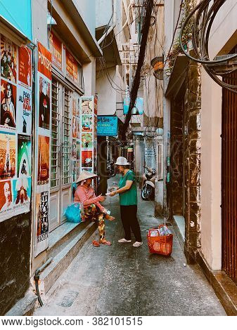 Saigon, Vietnam - January 27, 2020: Two Vietnamese Women Friends Talking To Each Other. Street Vendo