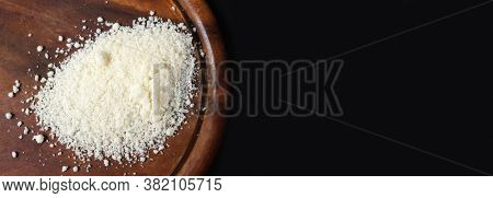Parmesan. Finely grated cheese on black background. Shredded Parmesan cheese