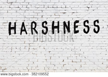 Inscription Harshness Written With Black Paint On White Brick Wall.