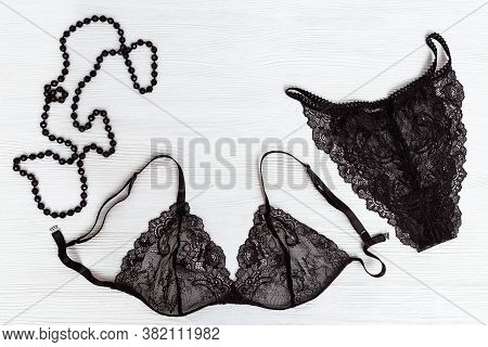 Black Lace Bra And Panty, Female Adornment Black Beads On White Wooden Background. Womans Lingerie.