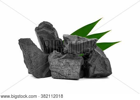 Natural Wooden Charcoal, Traditional Or Hard Wood Charcoal With Bamboo Leaves Isolated On White Back