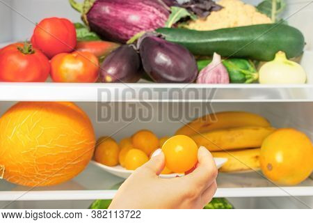 Woman's Hand Takes A Fruit From The Refrigerator. The Refrigerator Is Filled With Vegetables And Fru