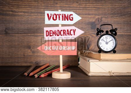 Voting , Democracy And Dictatorship Concept. Signpost With Arrows. Books, Alarm Clock And Pencils