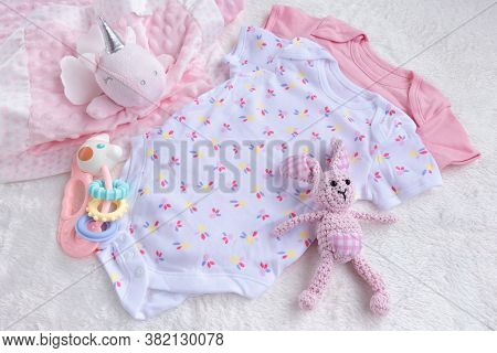 Baby Mockup. Bodysuits For Baby Girl And Rattle Toy On A White Fur Carpet. Newborn Baby Concept. Bab