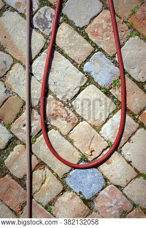 An image of a water hose on a cobble stone floor