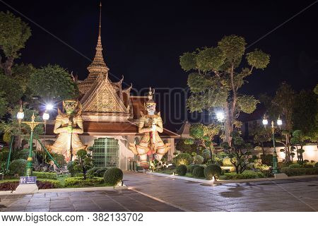 Wat Arun Temple Of Dawn Buddhist Temple With Guardians Protecting Gates. Bangkok, Thailand.