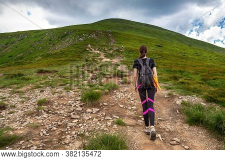 A Young Girl With A Backpack Climbs A Mountain. Beautifull Cloudy Sky. Leisure. Hiking. Hoverla Moun