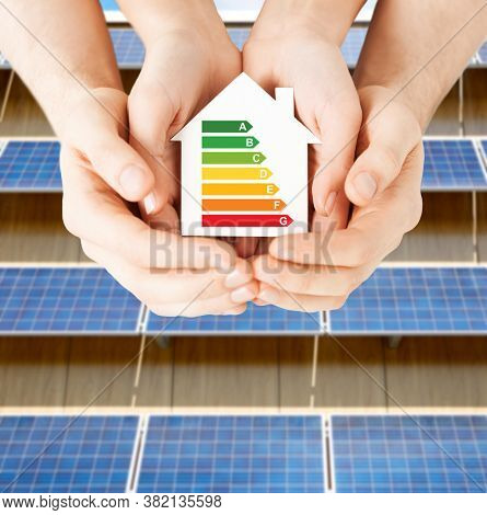sustainability and consumption concept - close up of couple hands holding white house with energy efficiency rating over solar panels on background