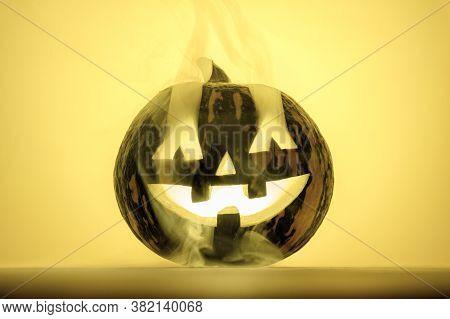 Happy Halloween. Funny Glowing Pumpkin Jack-o-lantern In The Smoke On A Yellow Background. Backlight