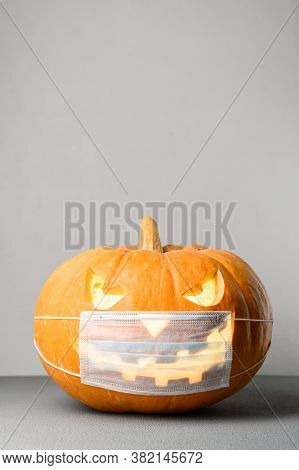 New Normal Concept. Glowing Halloween Pumpkin In A Protective Medical Mask On A Gray Background. Spa