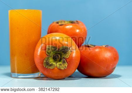 Persimmon Juice And Fresh Fruits On Blue Background