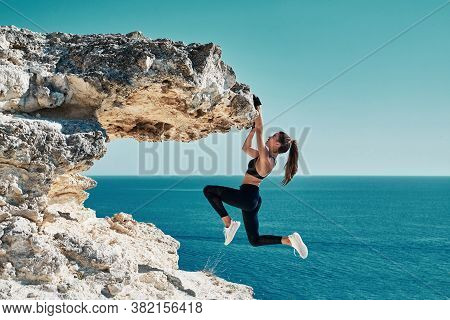 Rock Climbing. Sport. Active Lifestyle. Athlete Woman Hangs On Sharp Cliff. Seascape. Outdoors Worko
